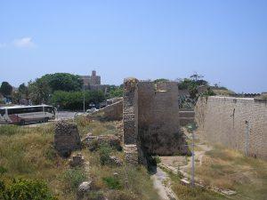 """שרידי חומת דאהר אל-עומר משמאל וחומת אל-ג'זאר מימין. ברקע מצודת עכו ומשמאל נראית ה""""מגלשה"""" דרכה גלשו המים אל תוך העיר"""