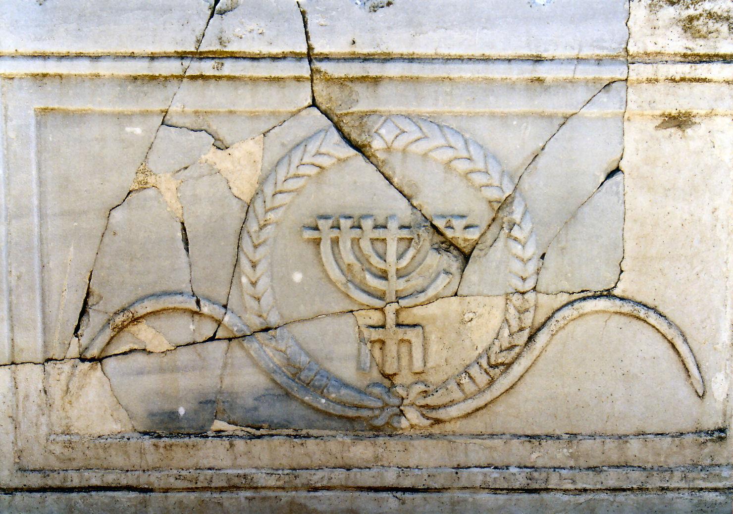 הסורג מאבן שיש, עם תבליט מנורת שבעת הקנים, שנמצא בבית הכנסת ביישוב העתיק רחוב, מוצב כיום בסמוך לרפליקת הפסיפס (צולם ב-1975) מקור: עוזי פז, יוצר:הינדה גלסנר