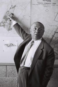 עובד בן עמי על רקע תכנית העיר אשדוד 1960
