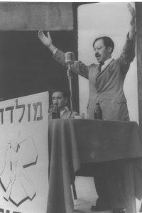 """בגין נואם לאחר יציאתו מהמחתרת, ב-14 באוגוסט 1948, בתל אביב. יושב לידו חיים לנדאו. מלפניו הכתובת """"מולדת וחרות"""" וסמל האצ""""ל."""
