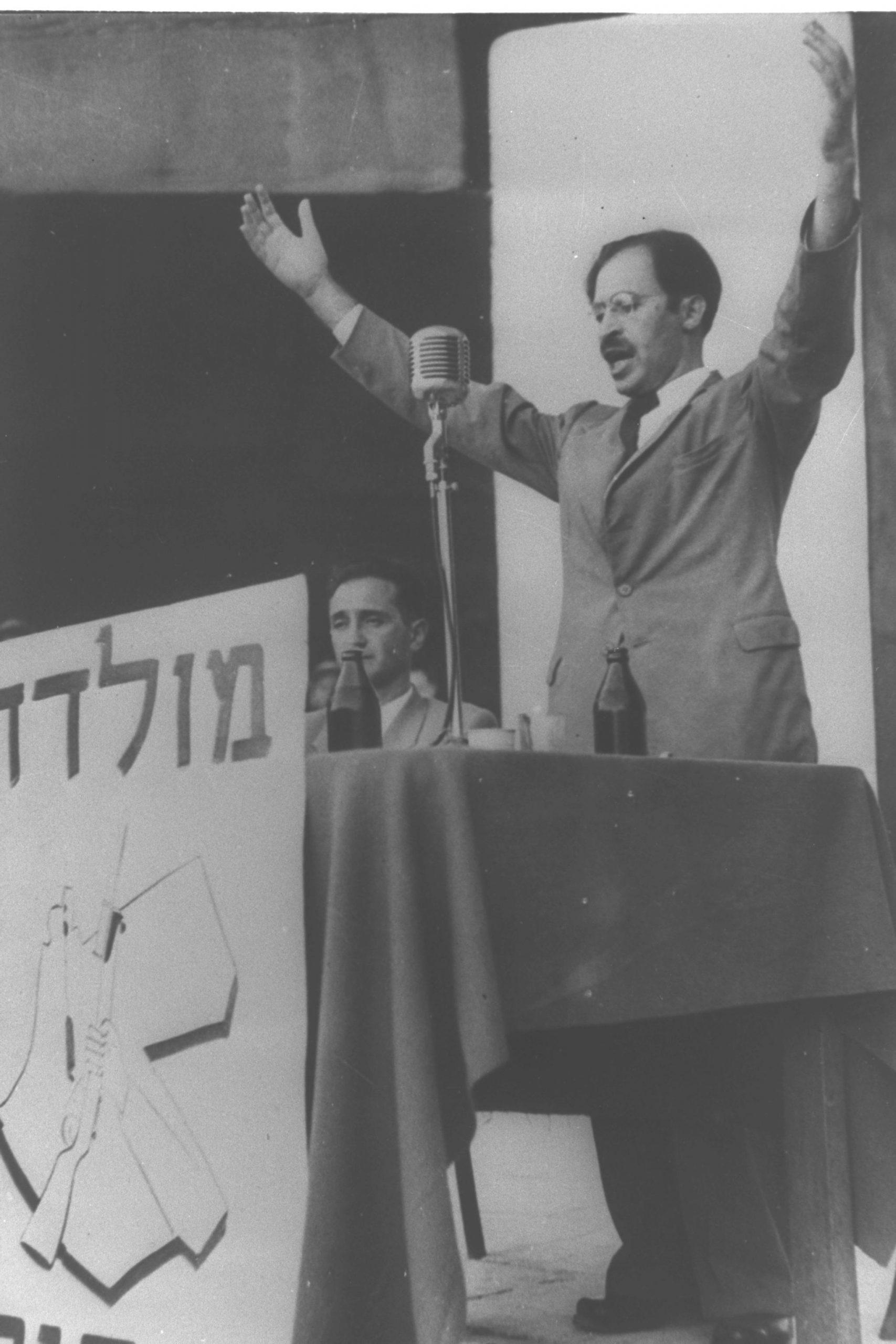בגין נואם לאחר יציאתו מהמחתרת, ב-14 באוגוסט 1948, בתל אביב. יושב לידו חיים לנדאו. מלפניו הכתובת